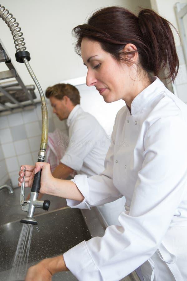 Female employee washing dishes at restaurant. Female employee washing dishes at the restaurant stock images