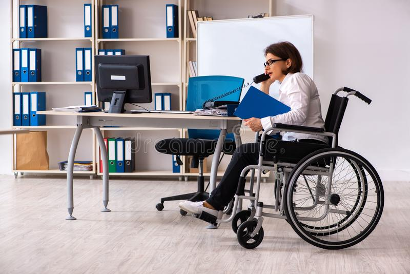 The female employee in wheel-chair at the office. Female employee in wheel-chair at the office stock photo