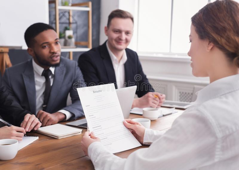 Female employer holding applicant resume at interview. Female employer holding applicant resume during office interview royalty free stock photo