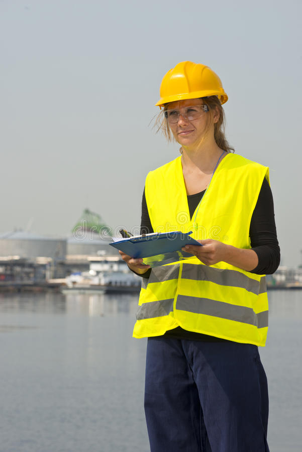 Female engineer. Feamale engineer with hard hat, safety goggles and a safety vest in a harbor district stock image