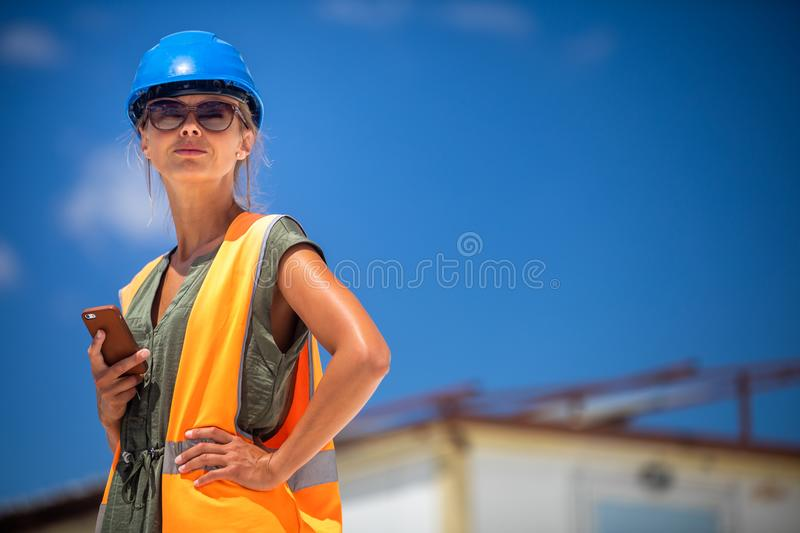 Female engineer architect with a safety helmet and a cell phone royalty free stock image