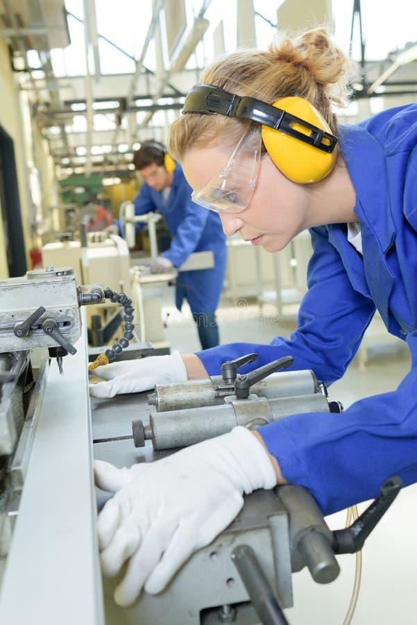 Female engineer drilling hole into metal. Engineer stock image