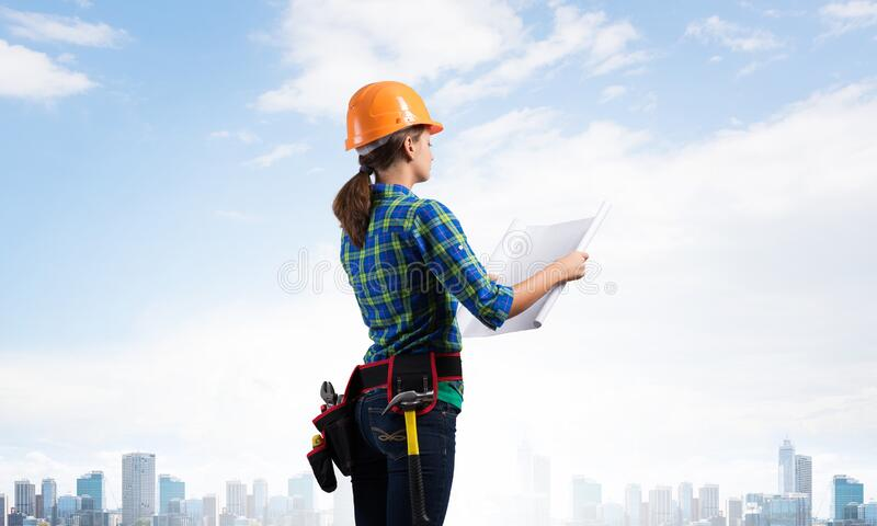 Female engineer in hardhat standing with blueprint royalty free stock photos
