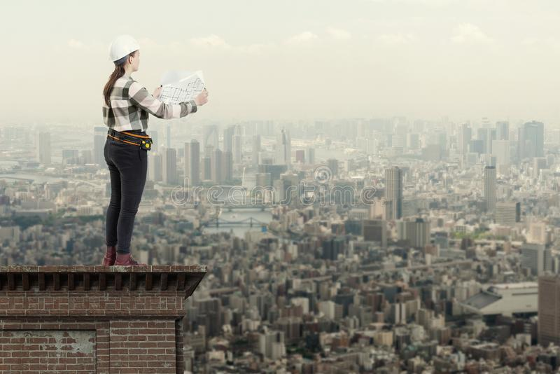 Female engineer holding construction plans standing on the roof top above a city stock images