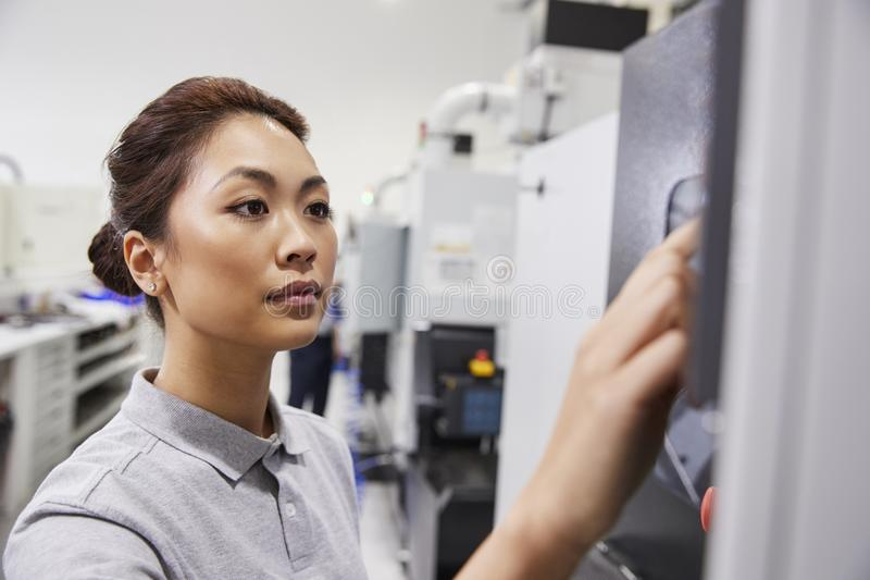 Female Engineer Operating CNC Machinery In Factory royalty free stock photo