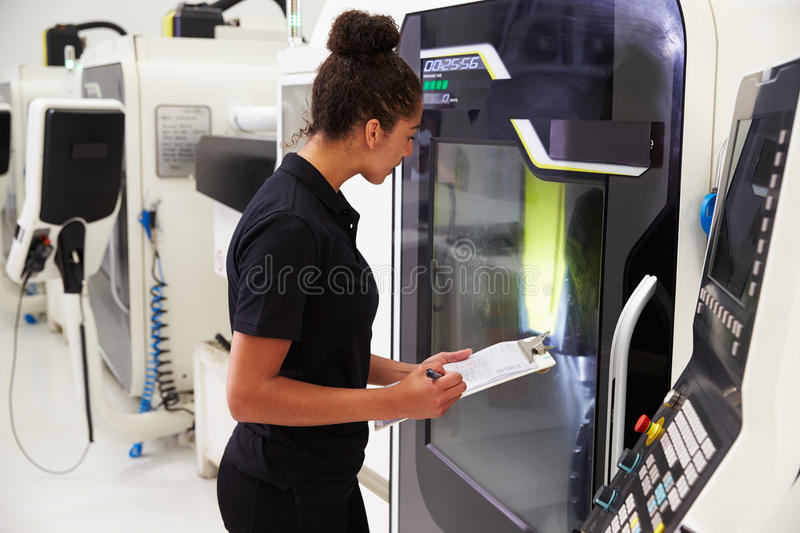 Female Engineer Operating CNC Machinery On Factory Floor royalty free stock image