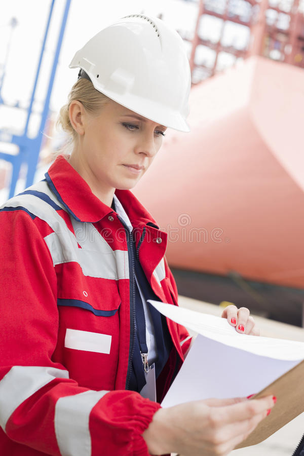 Female engineer reading documents in shipping yard stock photography