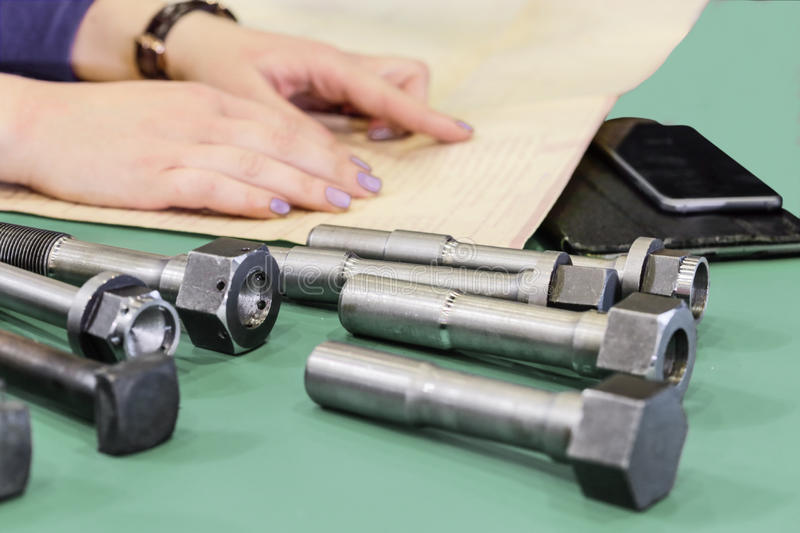 A female engineer reads the description and determines the appropriate fasteners. Bolts of various types and sizes widely used in mechanical engineering stock images