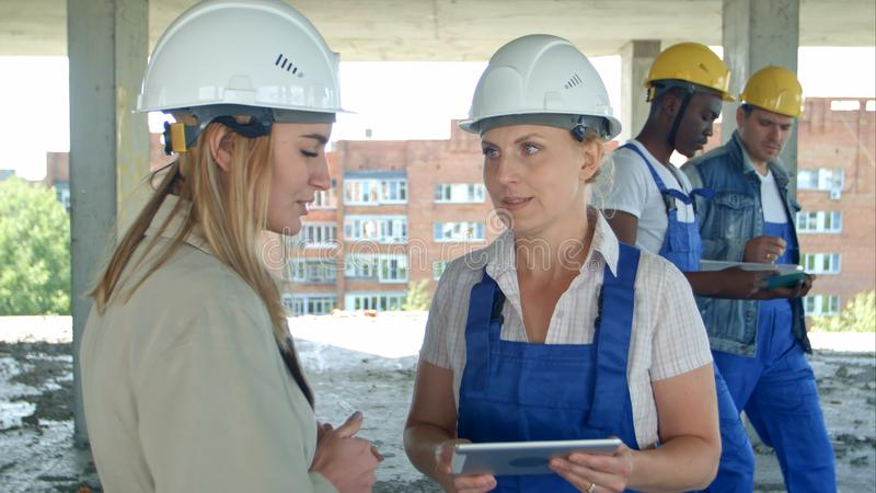 Female engineer and worker on construction site with plan on digital tablet royalty free stock photography