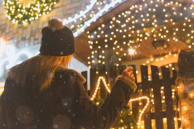 Female enjoying Christmas eve outdoors with sparklers stock photo