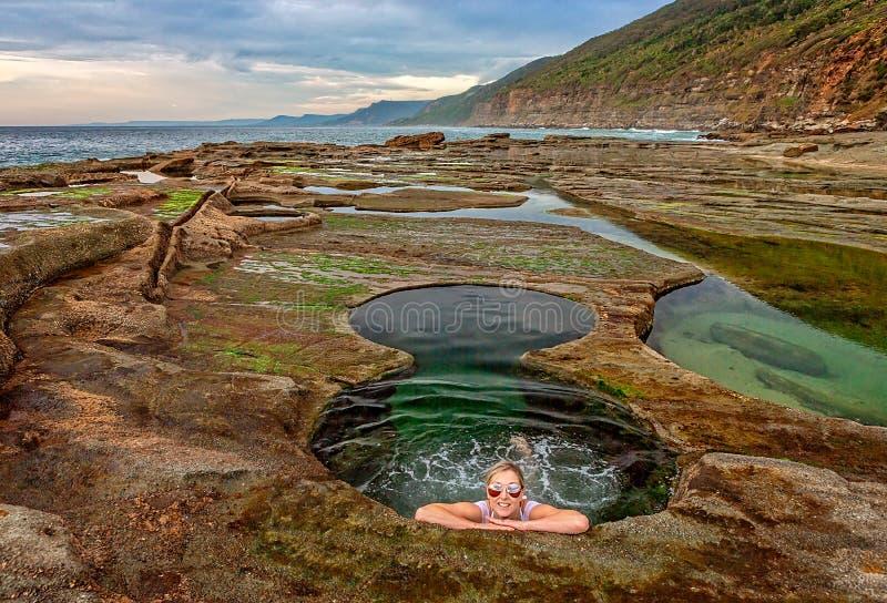 Female enjoying Figure 8 Pools on coastal rock shelf royalty free stock photography