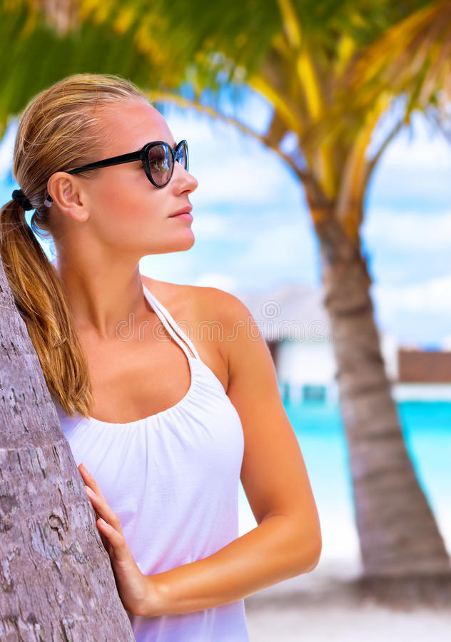 Female enjoying tropical beach. Portrait of attractive female wearing stylish sunglasses hug palm tree trunk, luxury summer vacation, travel and tourism concept royalty free stock image