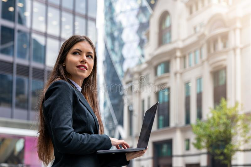 Female entrepreneur in front of office buildings. Successful businesswoman outdoors in the City working on a laptop; young, female entrepreneur in front of stock image