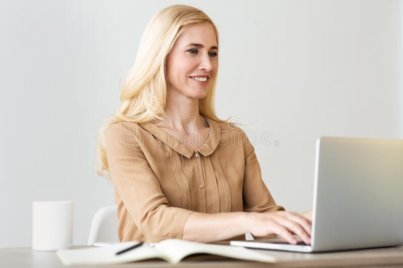 Female entrepreneur. Middle-aged businesswoman typing on laptop royalty free stock photos