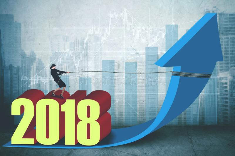 Female entrepreneur with number 2018 and arrow. Female entrepreneur pulling an upward arrow while standing above number 2018 with growth graph and modern city vector illustration
