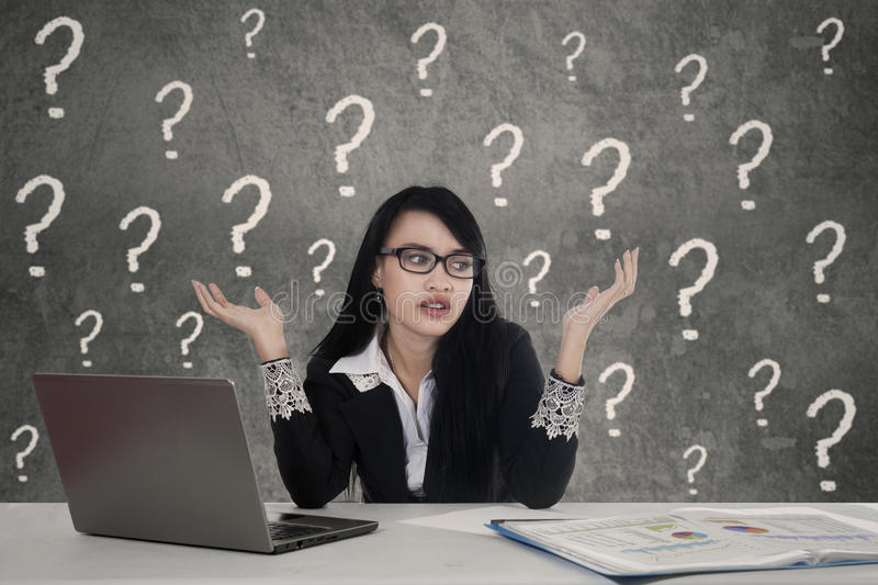 Female entrepreneur with question marks in office stock image