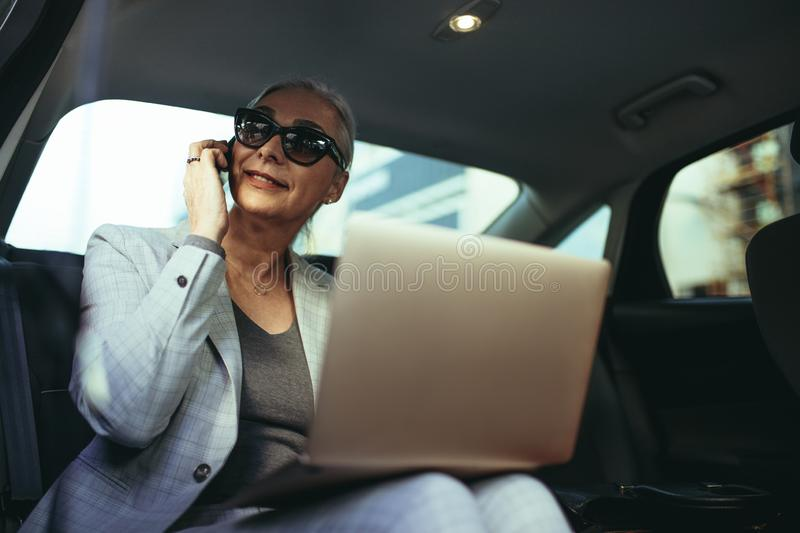 Female entrepreneur traveling to office in a luxury car royalty free stock photo