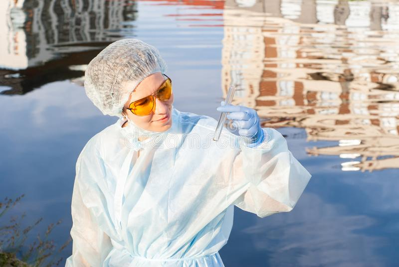 Female epidemiologist looks at a test tube with water from a city river. Female epidemiologist looks at a test tube with water against the background of a water royalty free stock photos