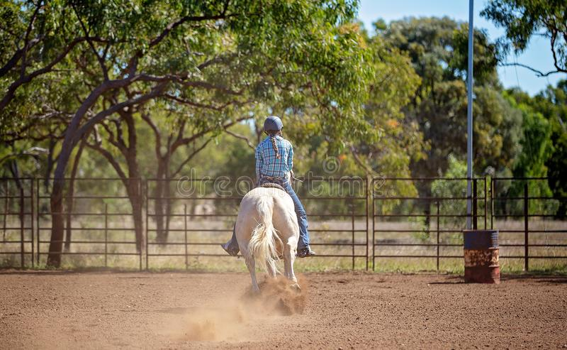 Cowgirl Competing In Barrel Racing Competition At Country Rodeo. Female equestrian competing in barrel racing in dusty arena at outback country rodeo royalty free stock photo