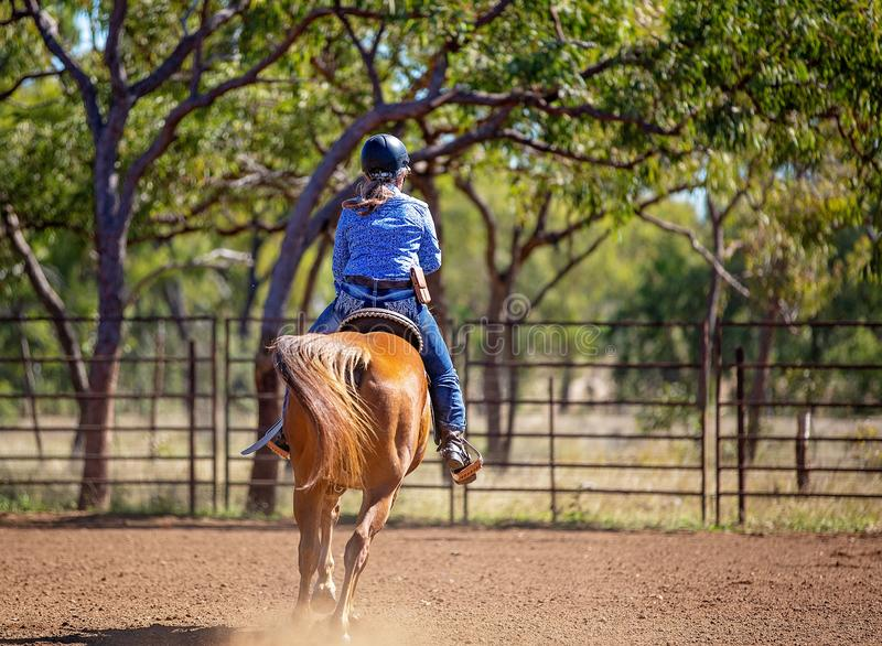 Cowgirl Competing In Barrel Racing Competition At Country Rodeo. Female equestrian competing in barrel racing in dusty arena at outback country rodeo royalty free stock images