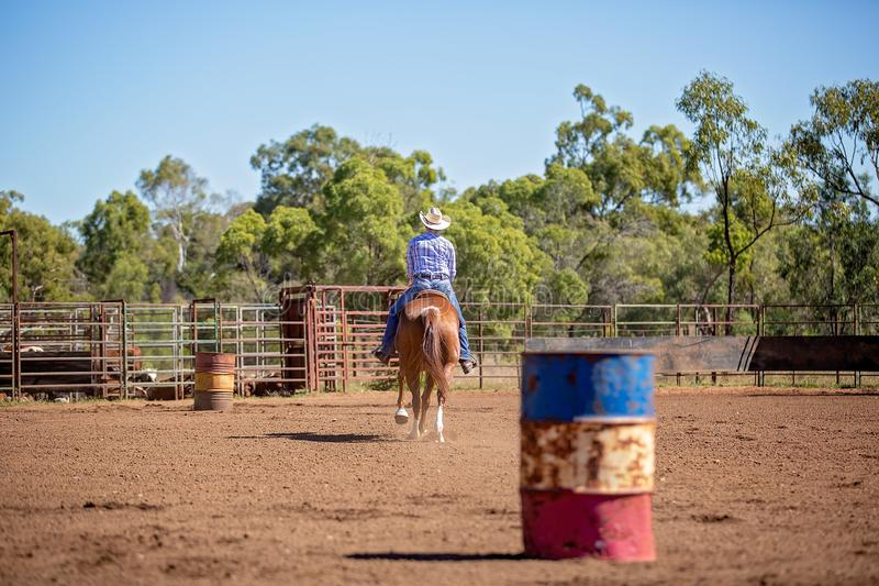 Cowgirl Competing In Barrel Racing Competition At Country Rodeo. Female equestrian competing in barrel racing in dusty arena at outback country rodeo royalty free stock photography