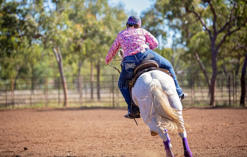 Horse And Rider Competing In Barrel Race At Outback Country Rodeo. Female equestrian competing in barrel racing in dusty arena at outback country rodeo stock photography