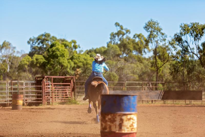 Horse And Rider Competing In Barrel Race At Outback Country Rodeo. Female equestrian competing in barrel racing in dusty arena at outback country rodeo stock image