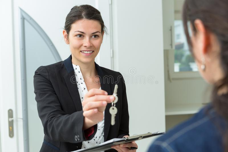 Female estate agent passing keys to client stock photography