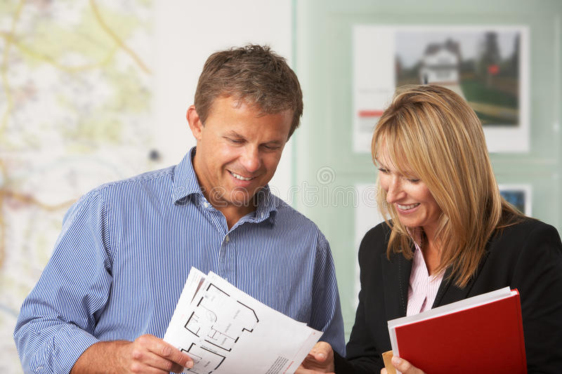 Female Estate Discussing Details With Client. Female Estate Discussing Property Details With Client royalty free stock photos