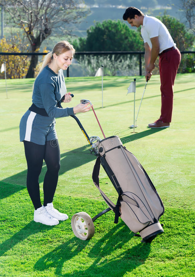 Female examining clubs while male hitting ball stock images