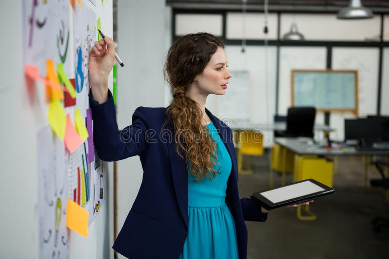 Female executive giving presentation while using digital tablet royalty free stock photo