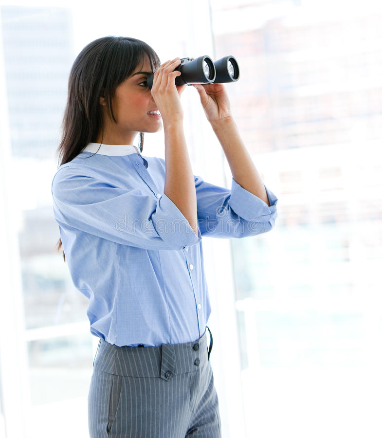 Female executive looking through binoculars royalty free stock photo
