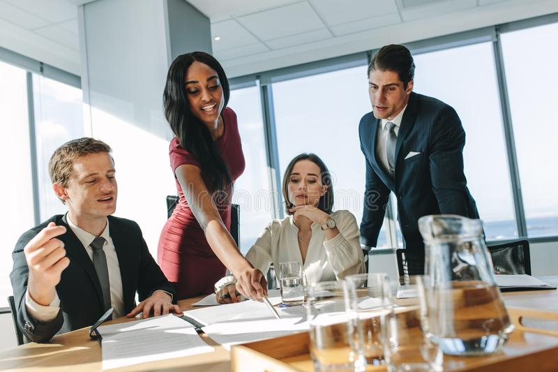 Corporate professionals during meeting in board room. Female executive pointing at a paper on table and putting her ideas during meeting . Group of corporate royalty free stock photos