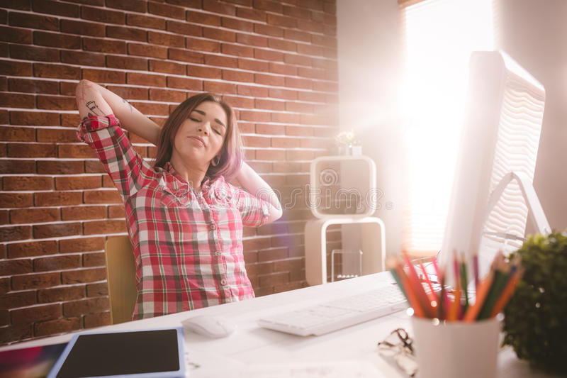 Female executive relaxing at her desk stock images
