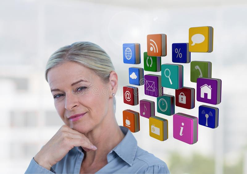 Female executive standing with hands on chin and appliction icons royalty free stock photo