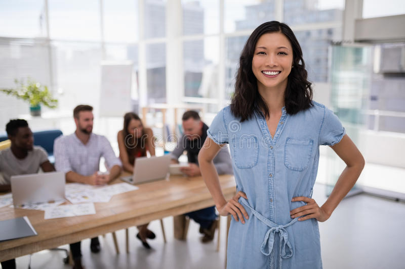 Female executive standing with hands on hip in the office royalty free stock photo