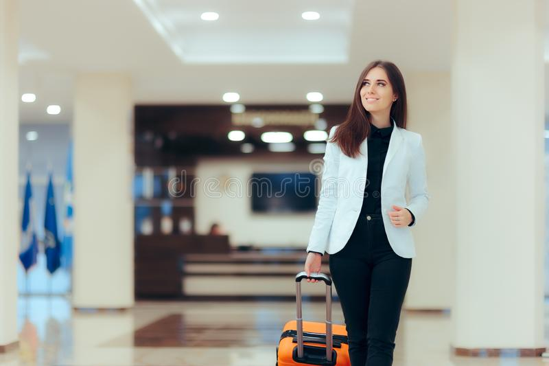 Elegant Business Woman with Travel Trolley Luggage in Hotel Lobby. Female executive with suitcase in work related business trip stock images