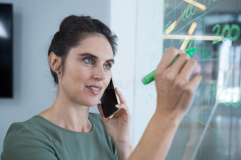 Female executive talking on mobile phone while writing on glass royalty free stock photo