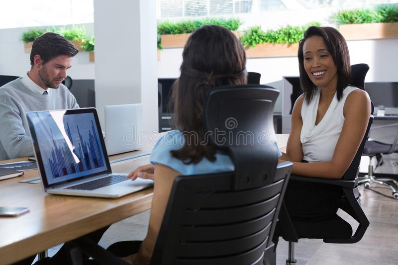 Female executive talking to each other at desk royalty free stock image