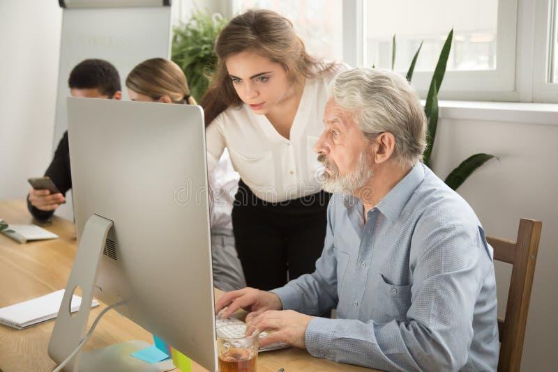 Female executive teaching senior office worker helping explainin stock photos