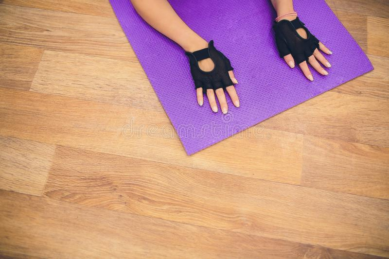 Female on exercise mat doing stretching workout. Focus on hand of a woman on fitness mat. royalty free stock photo
