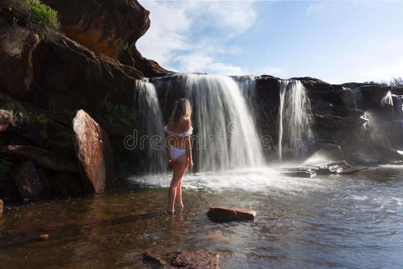 Female exploring and enjoying waterfalls and rock pools in nature stock image