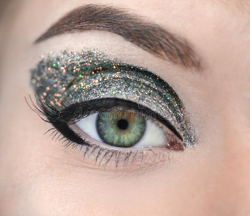 Female eye with fancy glitter makeup closeup stock image