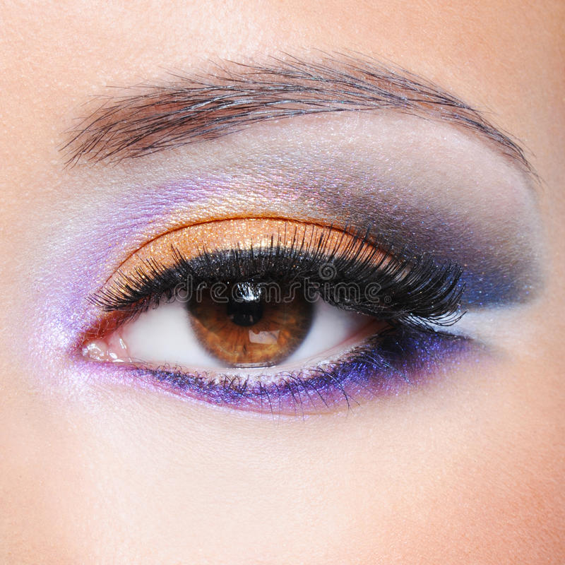 Female eye with fashion saturated make-up. Macro shot of a female eye with fashion saturated make-up stock photography