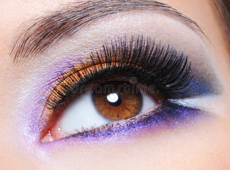 Female eye with fashion saturated make-up. Macro shot of a female eye with fashion saturated make-up royalty free stock images