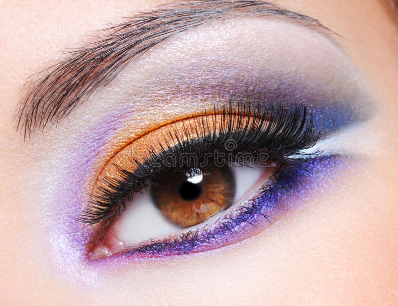 Female eye with fashion saturated make-up. Macro shot of a female eye with fashion saturated make-up royalty free stock photography