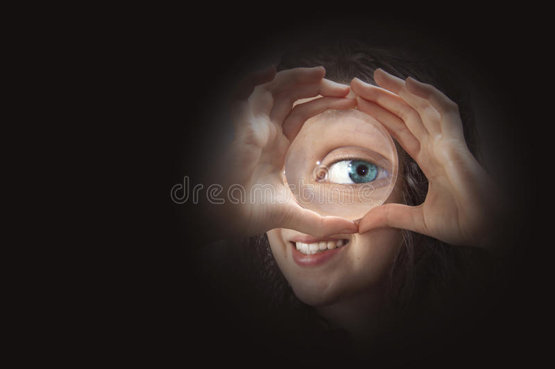 Female eye looking through magnifying glass close up royalty free stock photos