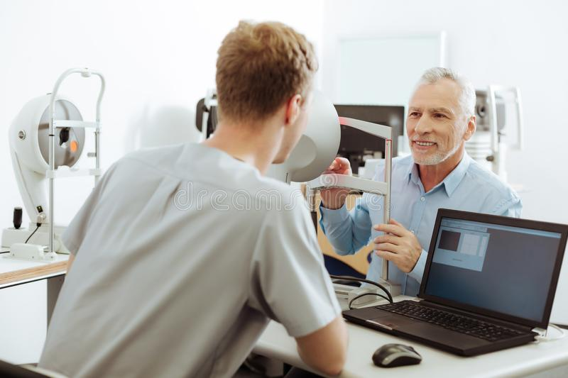 Female eye specialist sitting near laptop talking to her patient stock image