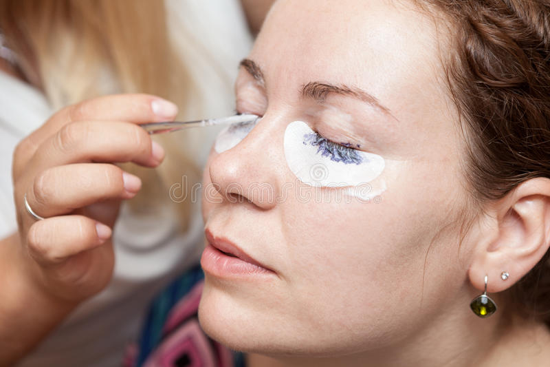 Female eyelashes dyeing with permanent blue makeup royalty free stock photo