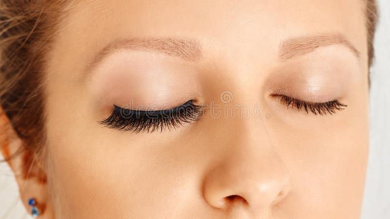 Female eyes with long false eyelashes, befor and after change. Eyelash extensions, make-up, cosmetics, beauty stock images